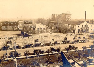 1920s photo. Long barracks in foreground. Alamo chapel in right background.