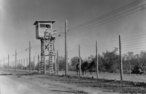 Ten-foot tall barbed-wire fence with guardhouse and horse patrols.